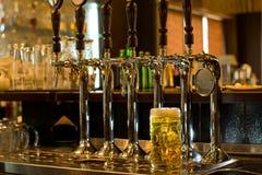 Tankard de bière avec de la bière tape dans un bar Photographie stock libre de droits