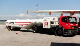 Tanken Sie Kerosin-LKW nahe bei einem Flugzeug an der Flughafenrollbahn wieder Lizenzfreie Stockbilder