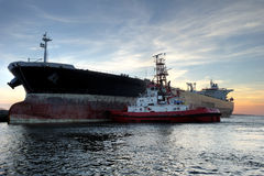 Tanker. With a tug at sunset Royalty Free Stock Photography