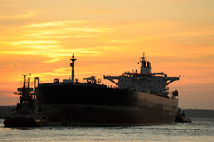 Tanker. At sunset in progress and being dragged out of the harbor Stock Image