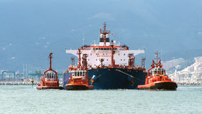 The tanker arrives in port. Tugs in action with the tanker Stock Photography