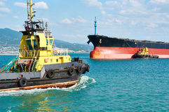 Tanker barge and powerful tugboats in sea Royalty Free Stock Image