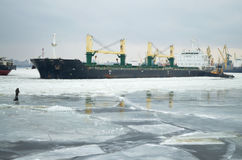 Tanker deploying tugs. A tanker makes a turn and pulls out of port royalty free stock photos