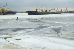 Tanker deploying tugs. The street is cold winter.The river has held down the ice stock photo