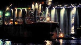 Tanker, der Raffinerie auf regnerischer Nacht führt stock footage
