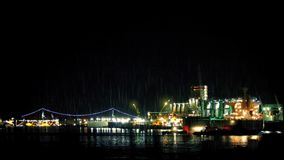 Tanker Docking Near City On Rainy Night. Large oil tanker moving slowly into bay next to industrial facility with suspension bridge in background stock video