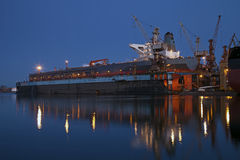Tanker in dry dock at night. A large tanker ship is being renovated in shipyard Gdansk, Poland Stock Image
