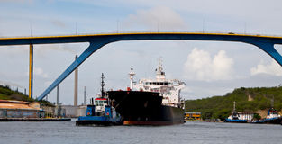Tanker mit dem Versuchsboot, das aus den Hafen herauskommt Lizenzfreie Stockfotografie