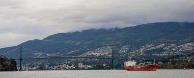 Tanker passes under Lion's Gate Bridge, Vancouver, BC. Royalty Free Stock Images