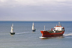 A tanker and sailing ships. A chemical/oil tanker passes two old sailing ships Stock Images