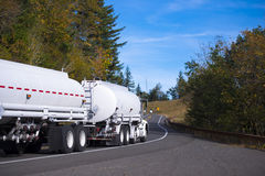 Tanker semi truck with two tank semi trailers on winding road. White New Big Rig semi-truck with two tank trailers for transportation of fuels and chemicals move Royalty Free Stock Photos