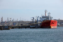 Tanker ship. Anchored on a dock and being loaded of gasoline Stock Image