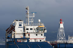 Tanker ship entering harbor. In faial island with lighthouse next to him Stock Photography