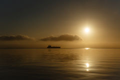 Tanker ship silhouetted on horizon at sunrise San Francisco Bay Royalty Free Stock Photos