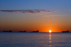 Tanker ship at sunset. Side view of silhouetted tanker ship with orange sunset background Stock Photography