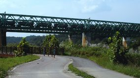 Tanker train  crossing a green truss bridge. Tanker train crossing a green truss bridge over a concrete walkway with trees and mountains in background under a stock footage