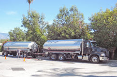 Tanker Truck. The driver of this Mack truck hauling two tanks of gasoline is preparing to off-load fuel into one of the underground tanks at the gas station Royalty Free Stock Photos