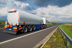 A tanker truck on the highway leading through the countryside Royalty Free Stock Images