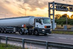 Tanker truck in motion on the motorway. With orange sky in the background royalty free stock photography