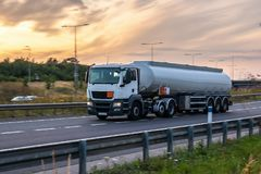 Tanker truck in motion on the motorway. With orange sky in the background stock image