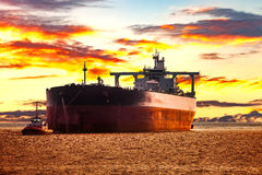 Tanker and tug. Tanker ship with escorting tugboat on sea at sunrise Royalty Free Stock Photography