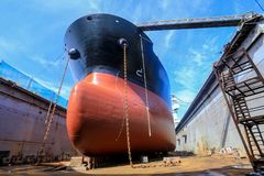 Tanker vessel on dock 5. Tanker vessel on dock for repair black and red color lower down her anchor on dock floor. Background blue sky royalty free stock photo