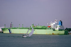 Tanker and yacht. Sailing yacht at full sail and the tanker moored at oil terminal Stock Photo