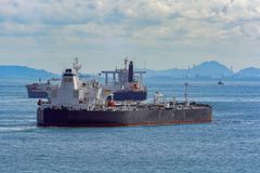 Tankers in front of an oil refinery plant royalty free stock photos
