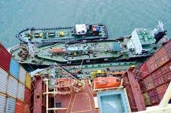 Tankerschepen opzij van groot containerschip stock afbeeldingen