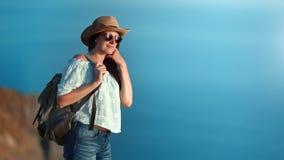 Tankfull kvinna för lyckligt lopp i hattsolglasögon som ser förbluffa havslandskap från berget stock video