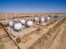 Tanklager für Massenerdöl- und Benzinspeicher Schattenbild des kauernden Geschäftsmannes Lizenzfreie Stockfotografie