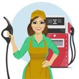 Tankstellearbeitnehmerin, welche die Tanksäule steht nahe bei Brennstoffzufuhr hält Lizenzfreies Stockbild