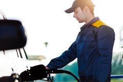 Tankstellearbeitskraft, die Auto an der Tankstelle wieder füllt Lizenzfreie Stockbilder