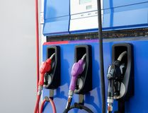 Tankt de close-up kleurrijke Hand die de auto met brandstof opnieuw vullen bij post, op witte achtergrond bij royalty-vrije stock fotografie