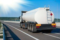 Tankwagen fährt auf Landstraße, weiße leere Farbe, hintere Ansicht, ein Gegenstand auf Straße lizenzfreies stockbild