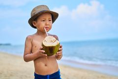Tanned Asian boy stands on the beach in a hat and drinks coconut stock photography