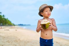 Tanned Asian boy stands on the beach in a hat and drinks coconut royalty free stock photo
