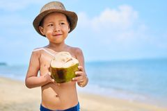 Tanned Asian boy stands on the beach in a hat and drinks coconut royalty free stock images