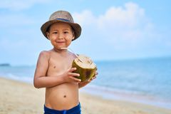 Tanned Asian boy stands on the beach in a hat and drinks coconut stock photo