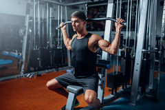 Tanned athlete workout on exercise machine in gym. Active training in sport club Stock Images