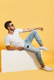 Tanned dude sitting on white box. Tanned bearded dude sitting on white box dressed in t-shirt and jeans wearing sneakers looking away Royalty Free Stock Photos