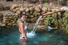 Tanned beautiful girl taking baths in hot springs. Stones in the background stock photo