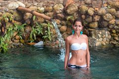Tanned beautiful girl taking baths in hot springs in white bikini. Stones in the background. Look at the left side stock photo