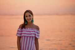 Tanned beautiful woman in dress with white and pink stripes. Close up and copy space. Orange sea or ocean at the sunset. Vacations. Concept royalty free stock images