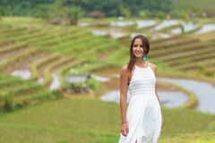 Tanned beautiful woman in white long dress smiling and posing against the background of rice fields. Close up stock images