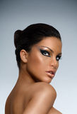 Tanned Beauty. Tanned model with expressive make-up over gray background Royalty Free Stock Image