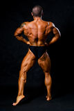 Tanned bodybuilder shows muscles of arms and back Stock Photo