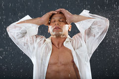 Tanned bodybuilder stands in rain. Tanned bodybuilder wearing white wet shirt stands in rain and holds with his head by hands. Andrei Popov is Bodybuilding Royalty Free Stock Images