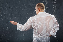 Tanned bodybuilder stands in rain. Tanned bodybuilder wearing white wet shirt stands in rain back to camera and catches drops by hand. Andrei Popov is Stock Photos