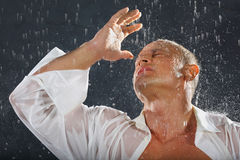Tanned bodybuilder stands in rain. Tanned bodybuilder wearing white wet shirt stands in rain and closed hand from drops. Andrei Popov is Bodybuilding Champion of Royalty Free Stock Image